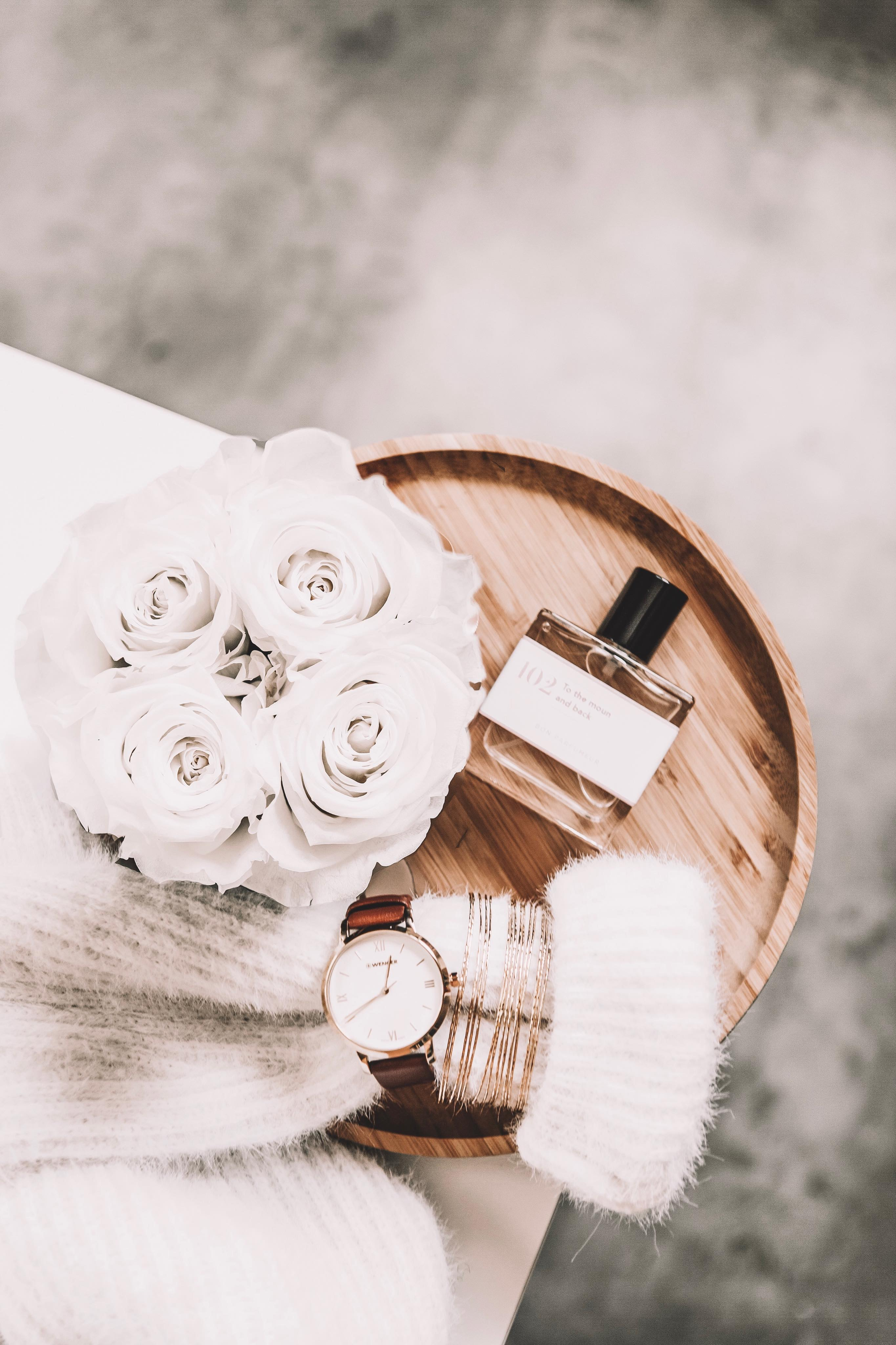 flat lay photography of fragrance bottle and bouquet of white flowers on round tray