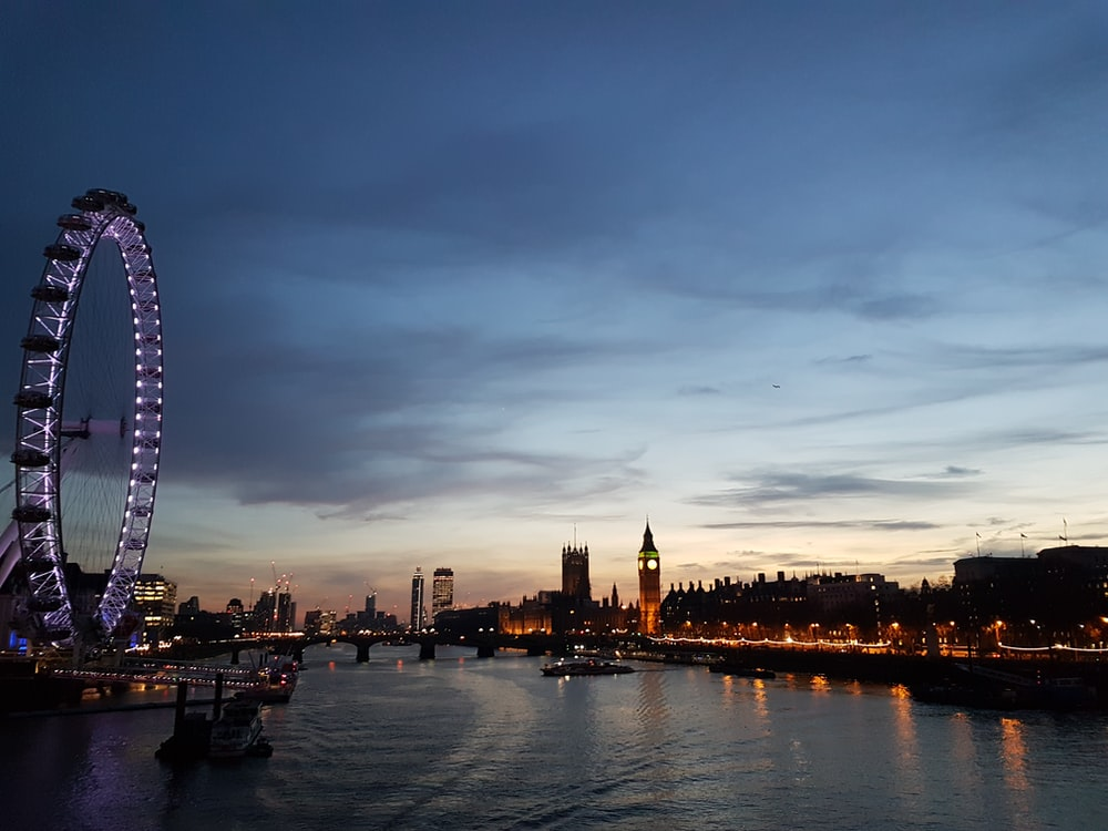 Ferris Wheel besides body of water during dawn