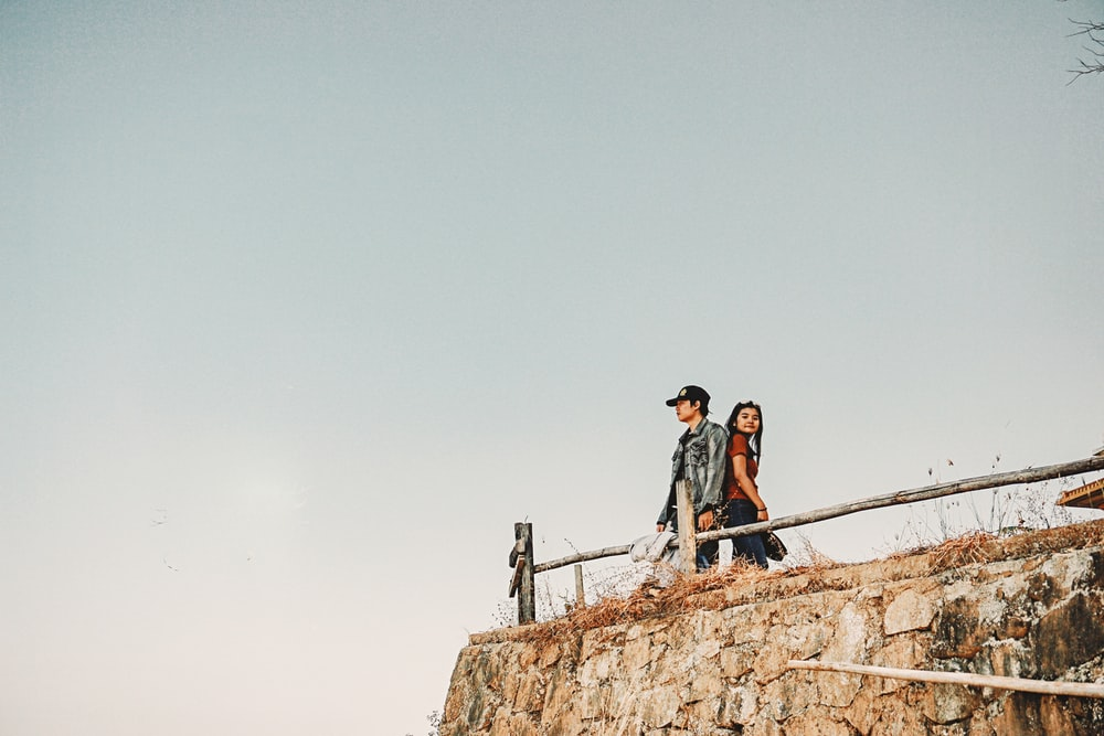 couple standing under white clouds