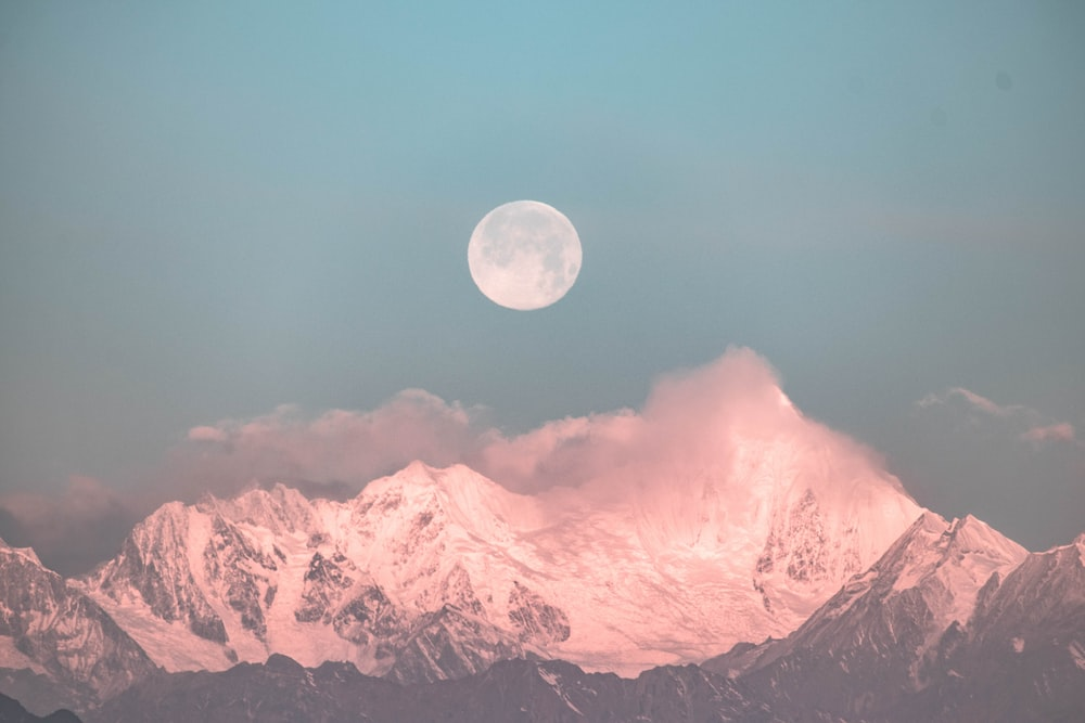 round moon over snow capped mountain ranges