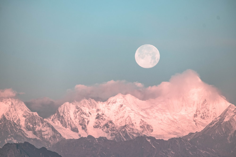 moon over snow covered mountains