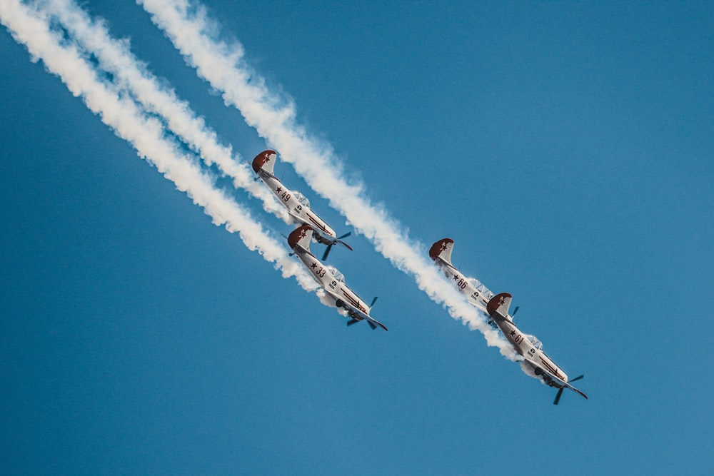 four airplanes flying on sky during daytime
