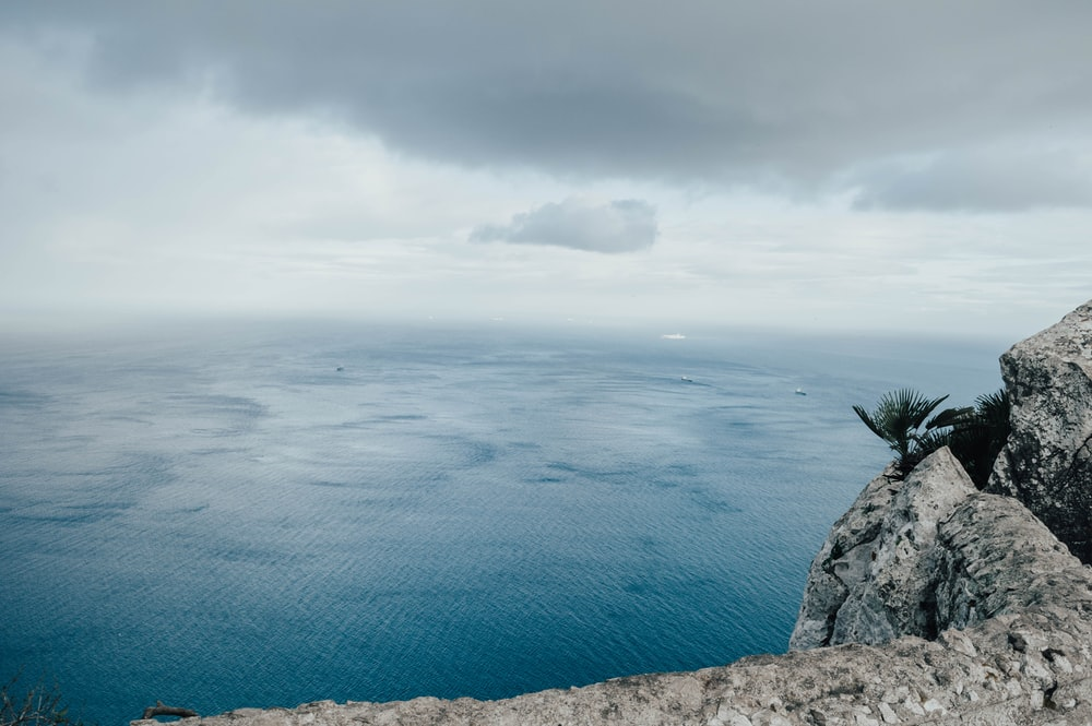 calm sea under gray clouds at daytime