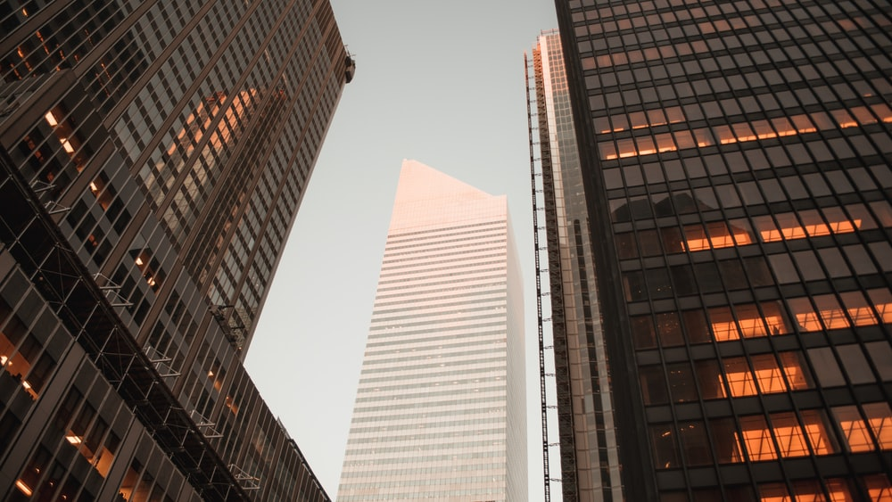 low-angle photography of gray high-rise building between two curtain wall high-rise buildings during daytime