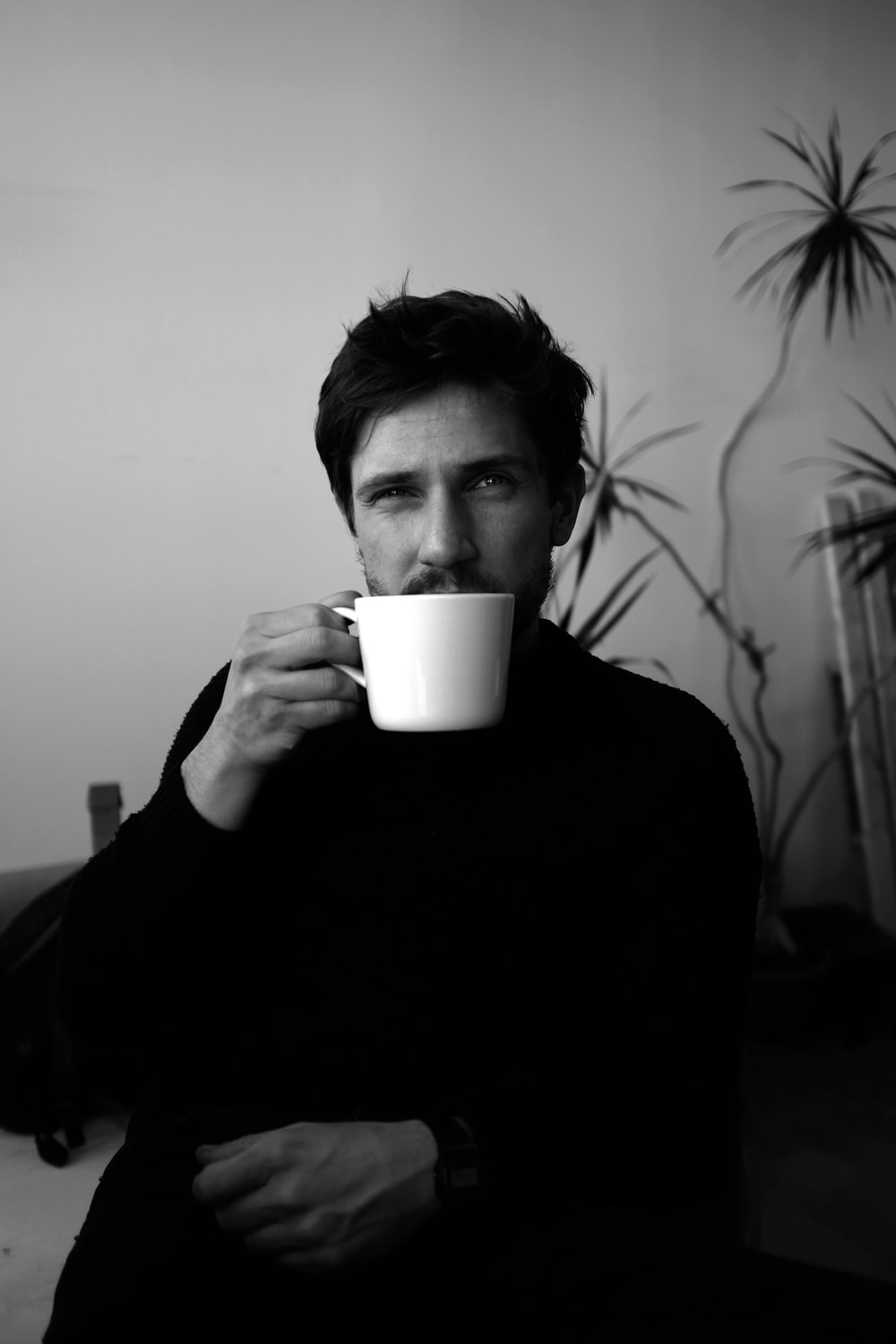 grayscale photo of man holding cup