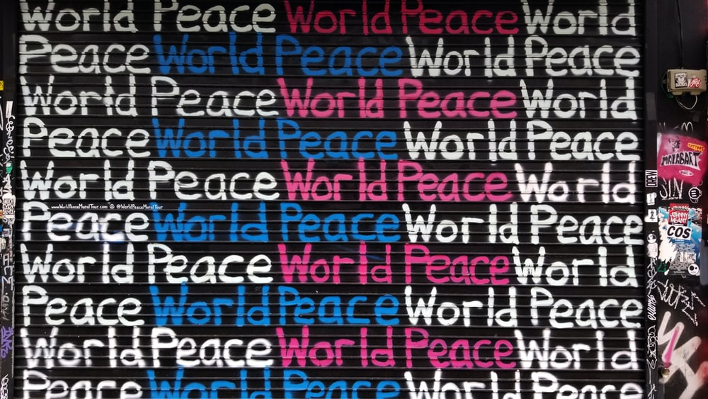 white, blue, and pink world peace painted wall