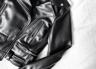 black leather zip-up jacket on white textile