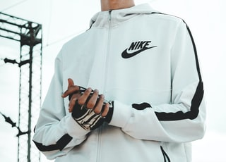 man wearing white and black full-zip Nike hoodie standing across electric cable wires