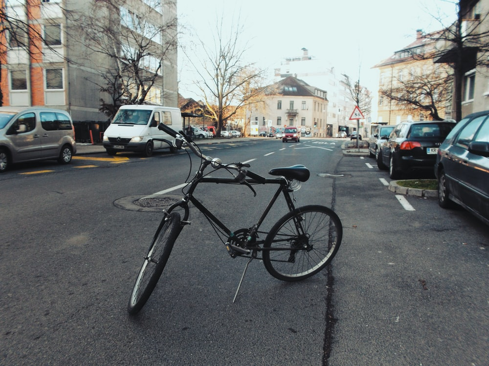black bicycle parked in middle of street
