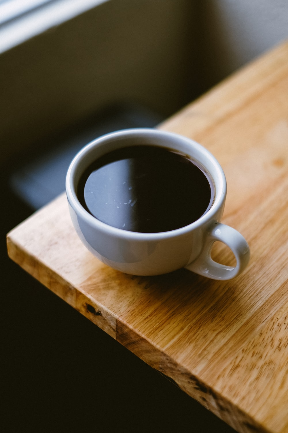 white coffee cup on brown wooden table