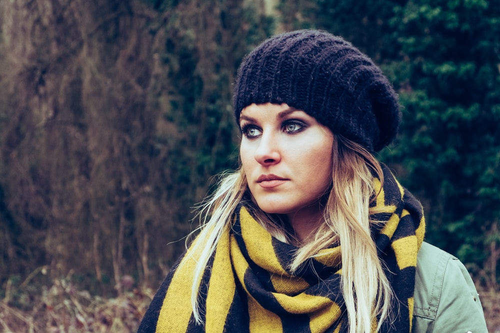 woman wearing black knit hat near trees