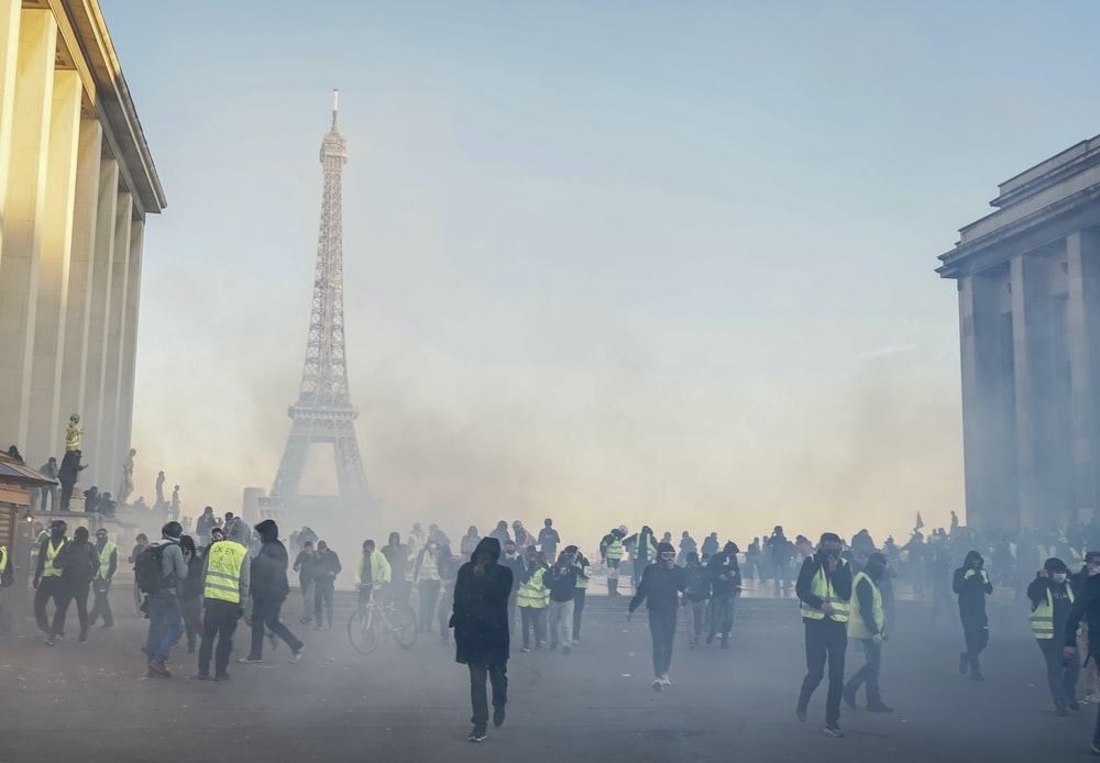 people wearing safety jackets near Eiffel Tower during daytime