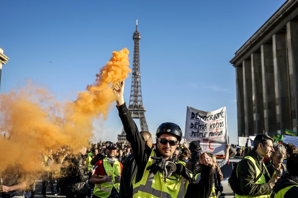 man standing and raising orange smoke on Paris during daytime