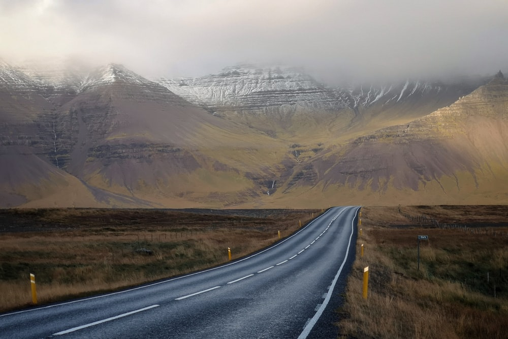 gray concrete road and brown mountains during daytime