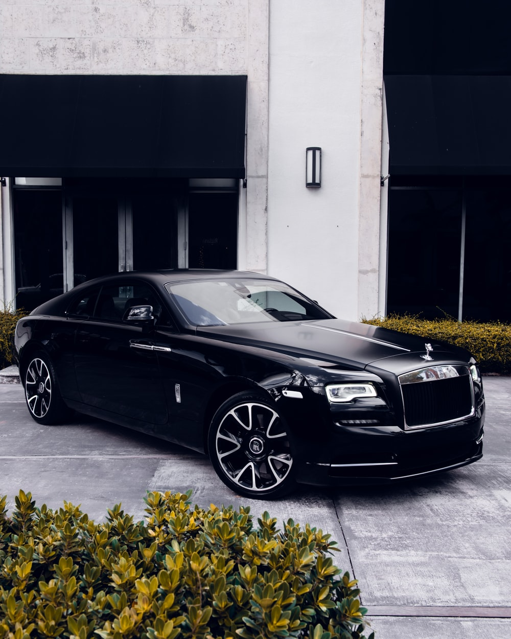 black coupe parked near building front