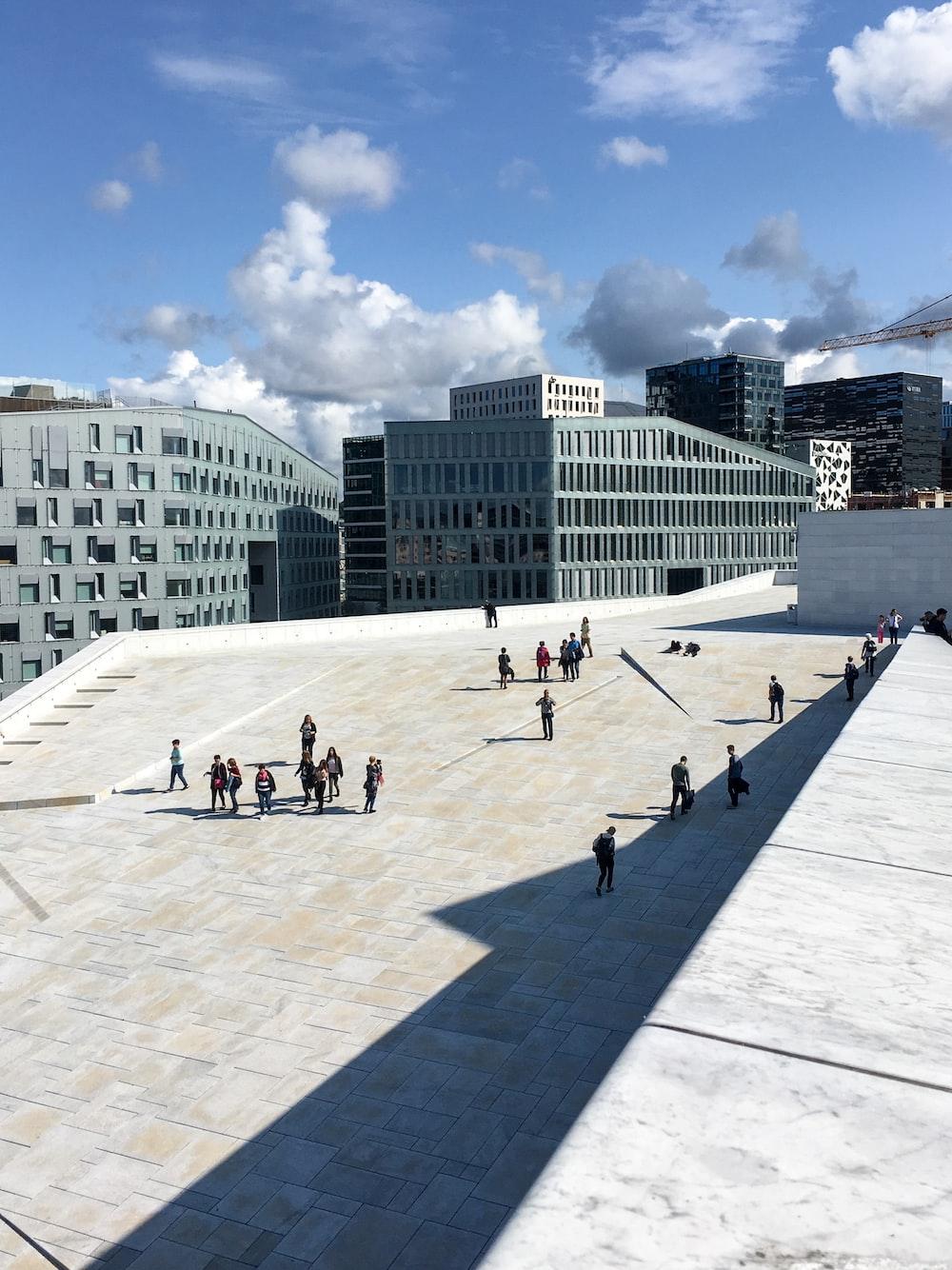 people outside gray concrete buildings