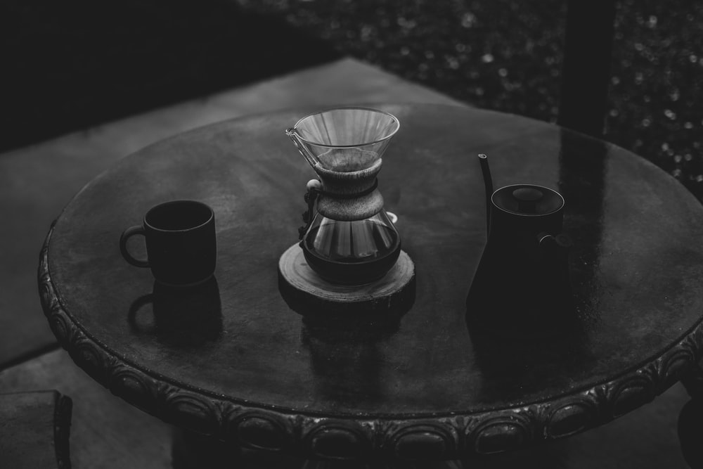 gray scale photo of mugs on round wooden table