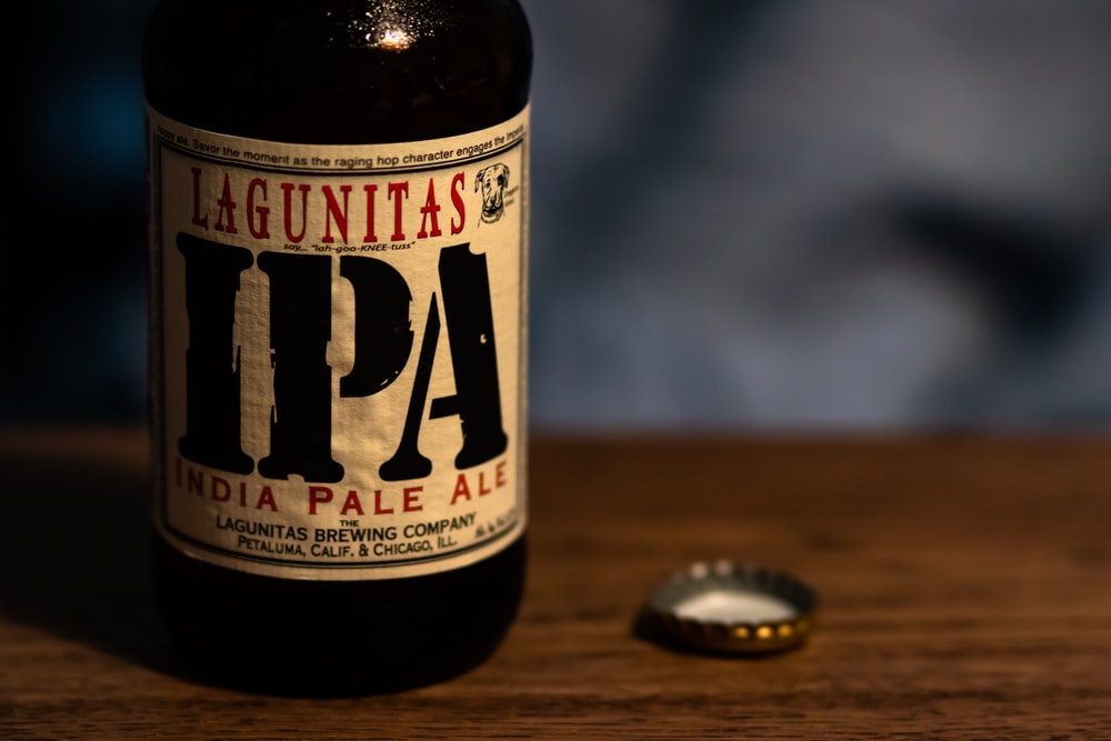 selective focus photography of Lagunitas IPA India Pale Ale bottle with bottle crown on tabole