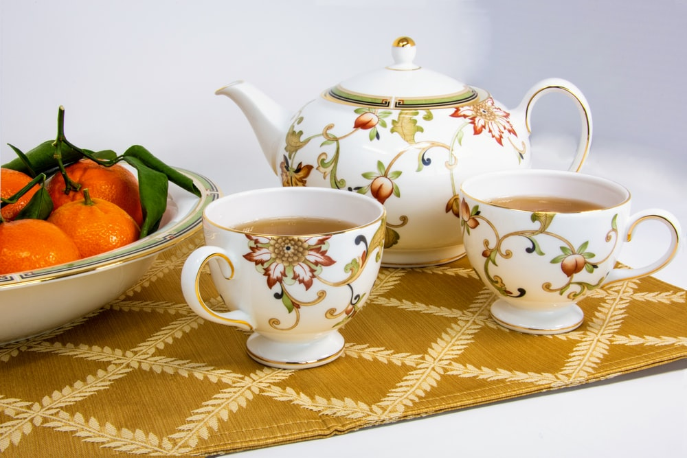 white-and-multicolored mugs filled with tea beside fruits