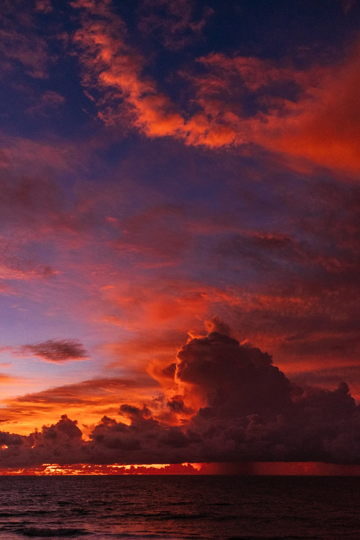 ocean under orange colored clouds