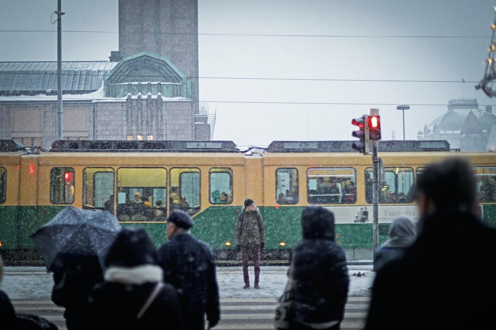 man standing beside yellow and green subway