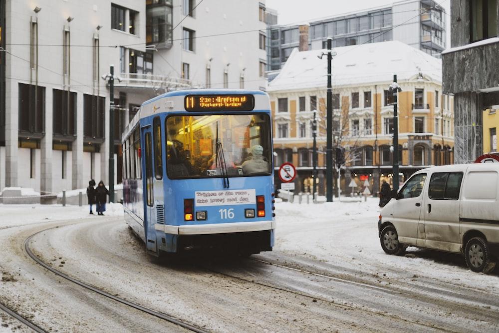 blue bus passing through building