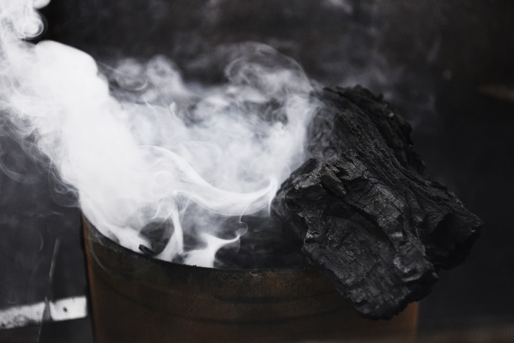 black charcoal with smoke on brown container