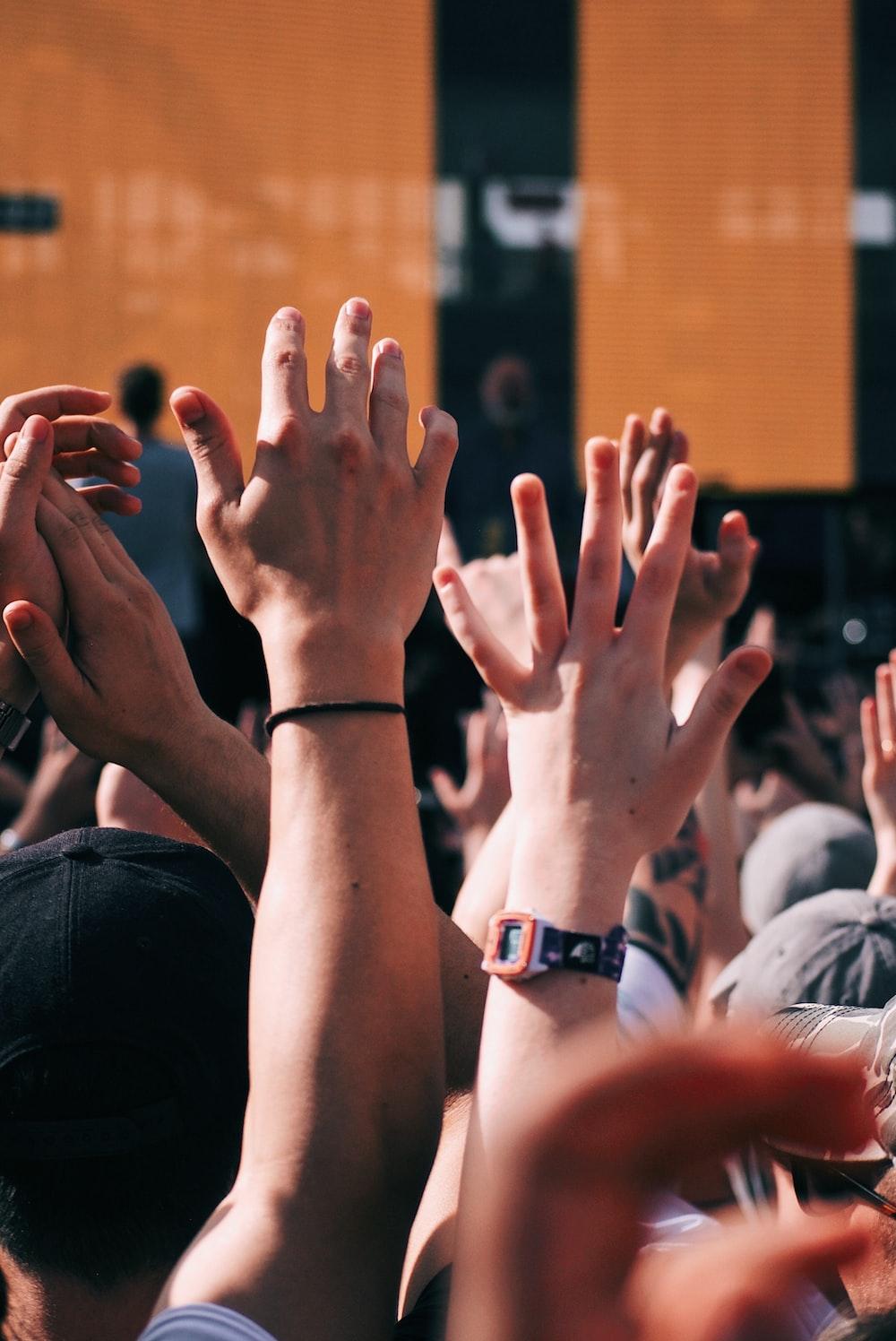 crown of people raising hands