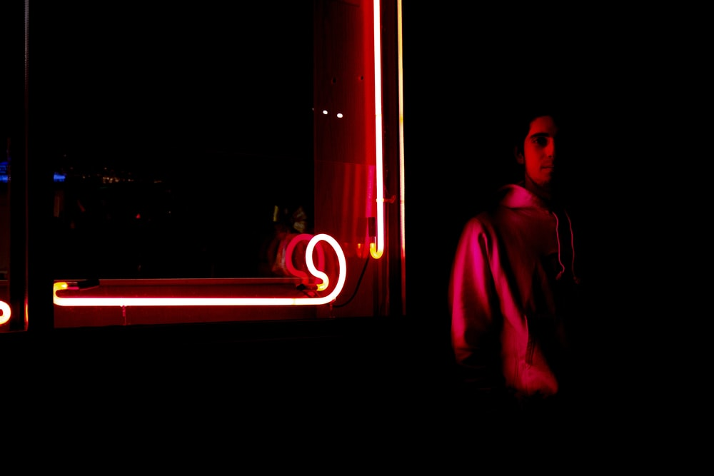man standing near red neon light