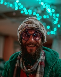 selective focus photography of man wearing gray knit cap, red-and-gray scarf and green cable knit zip hoodie
