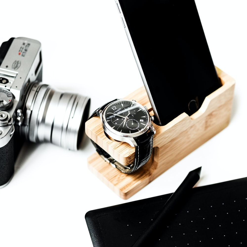 round silver-colored and black chronograph watch with leather band and iPhone