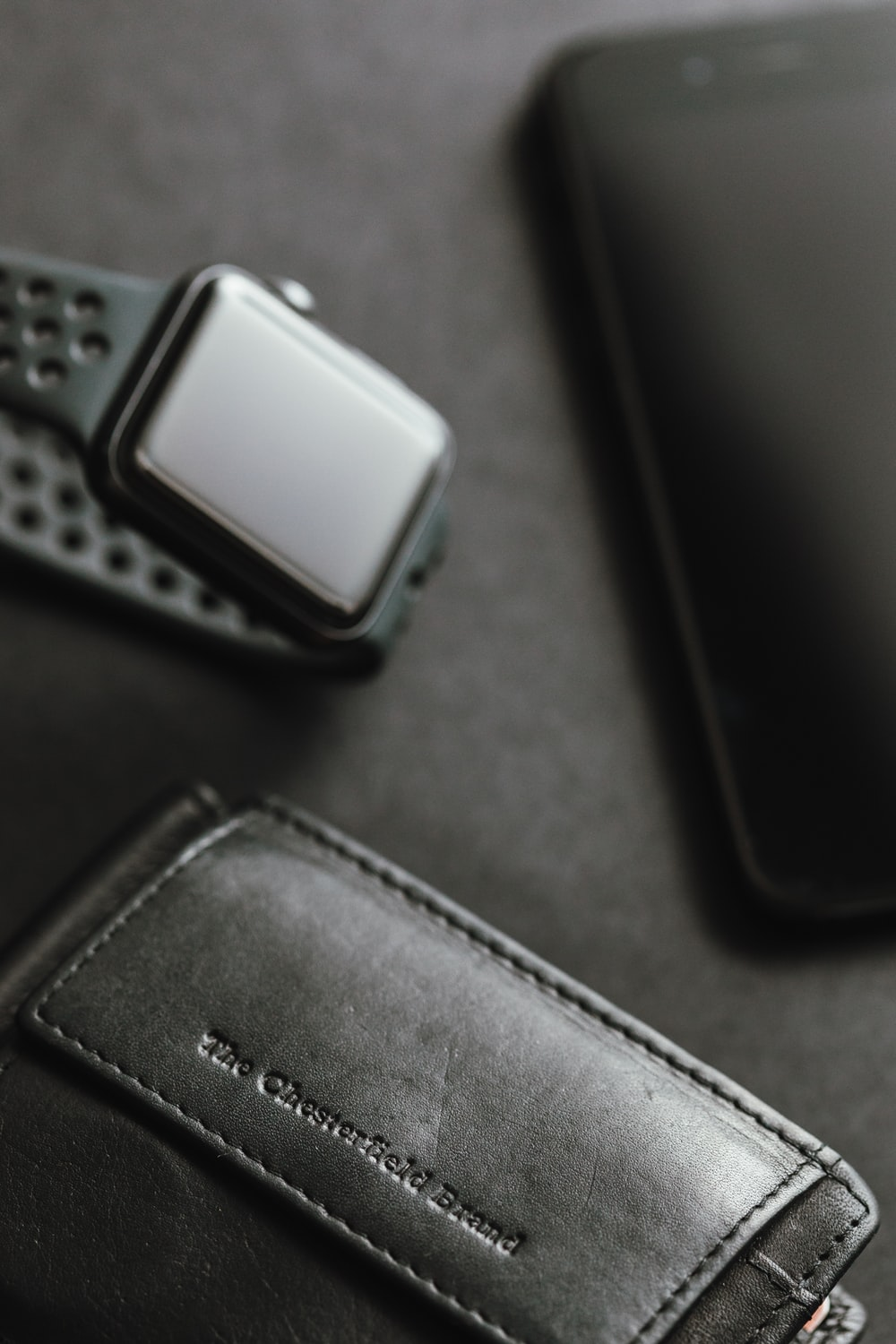 black leather wallet near space black aluminum case Apple Watch with gray Nike Fuel Band