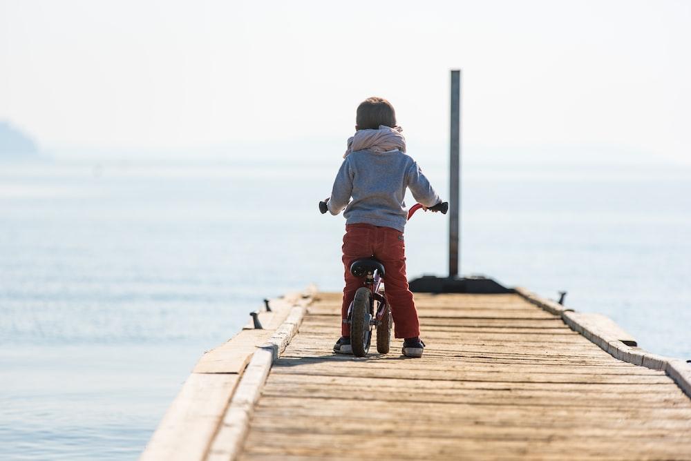 toddler wearing white scarf riding bicycle on brown dockl