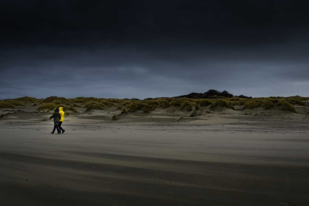 two person walking on desert