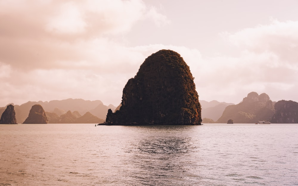 rock islands and calm sea during daytime