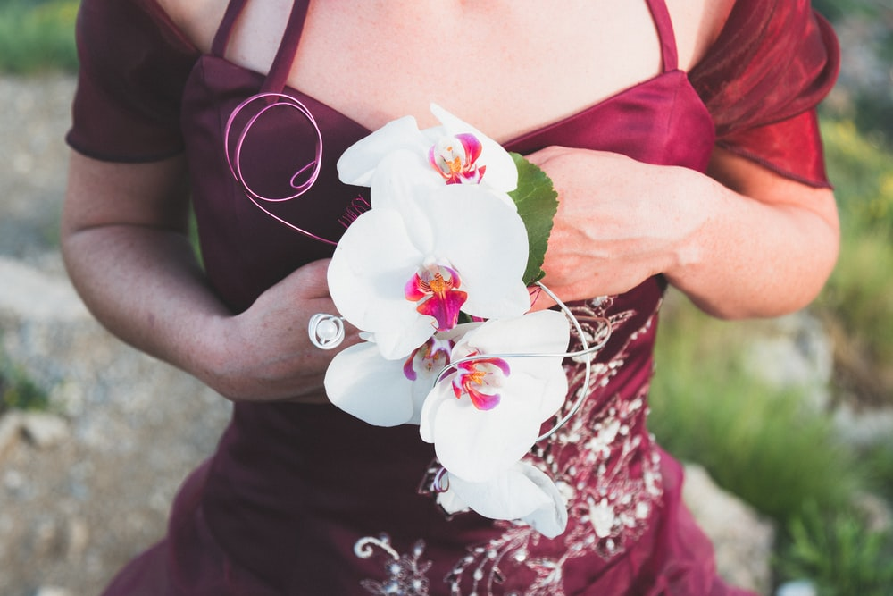 woman wearing red dress holding white orchids