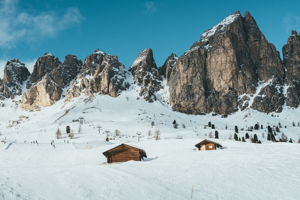brown cabin surrounded by snow near snow-capped mountains