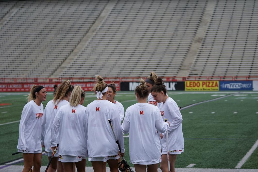 group of woman standing in lacrosse field