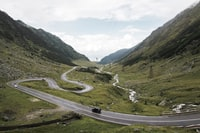 aerial photography of vehicle traveling on road near mountains