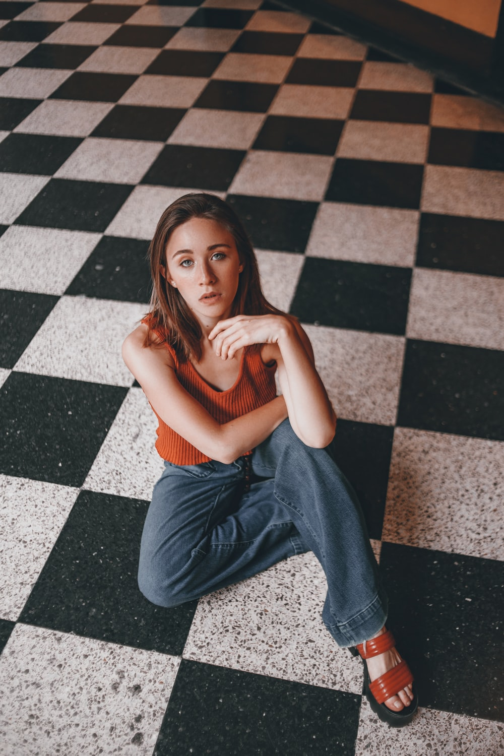 woman in brown tank top and blue jeans sitting on floor