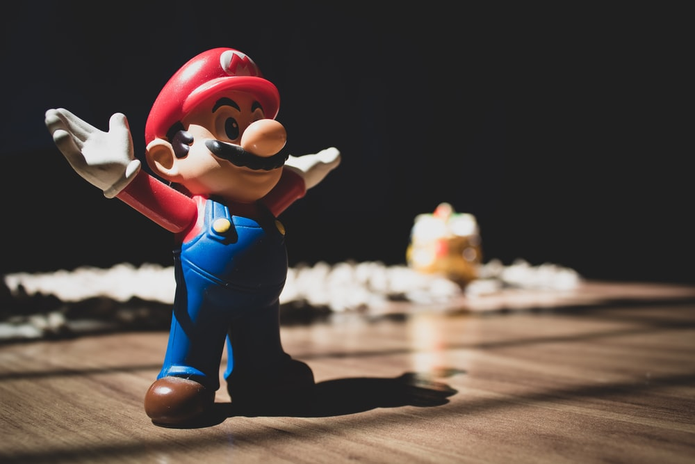 Super Mario figurine on brown surface