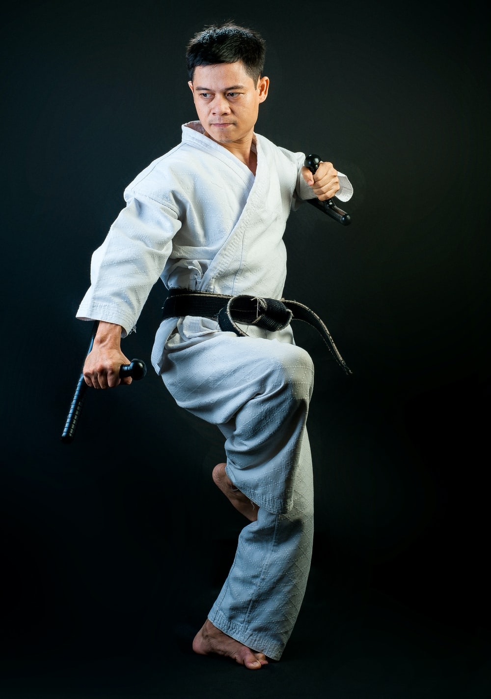 Black belt martial artist standing with one leg