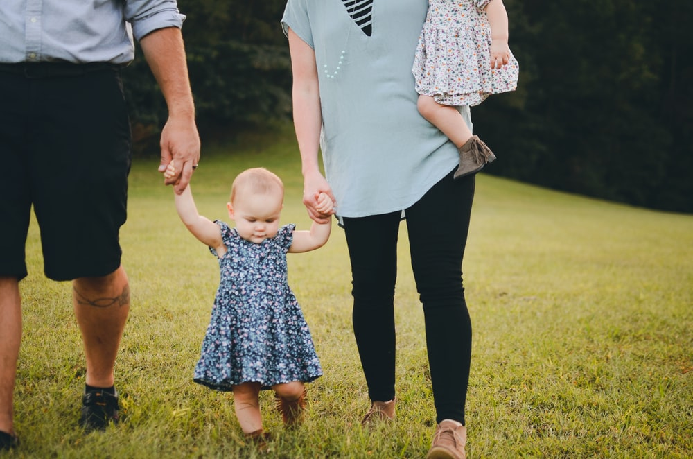 couple holding baby's arm walking on grass field