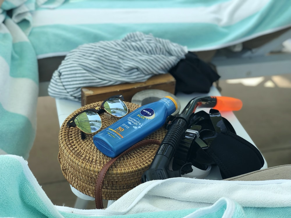 blue labeled bottle and brown wicker bag