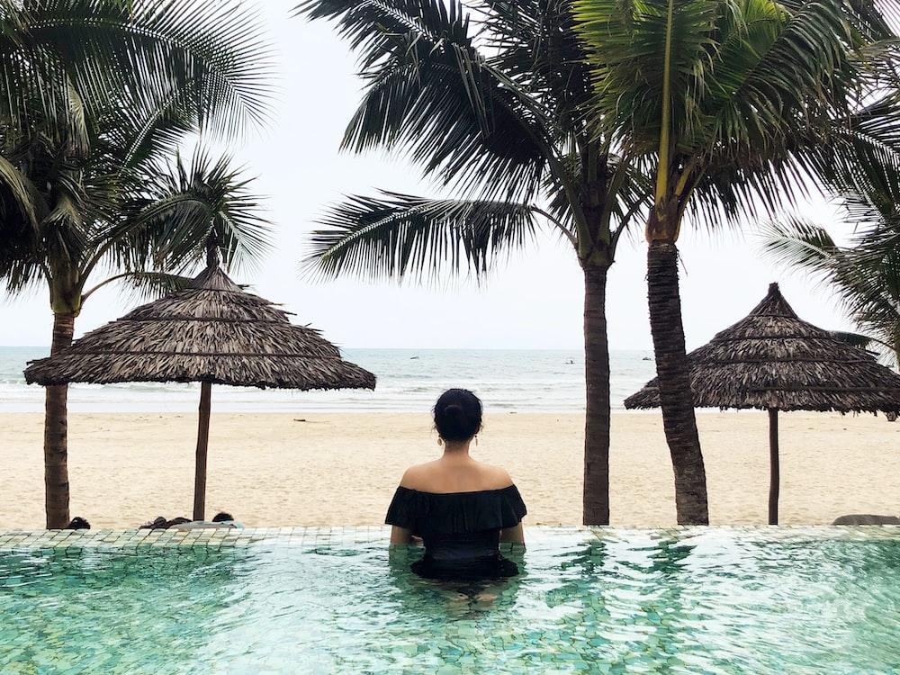 woman in pool looking on sea