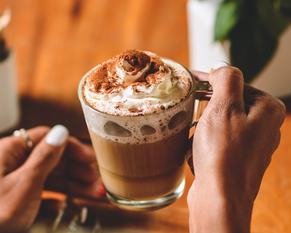 person holding mug with chocolate beverage and cream