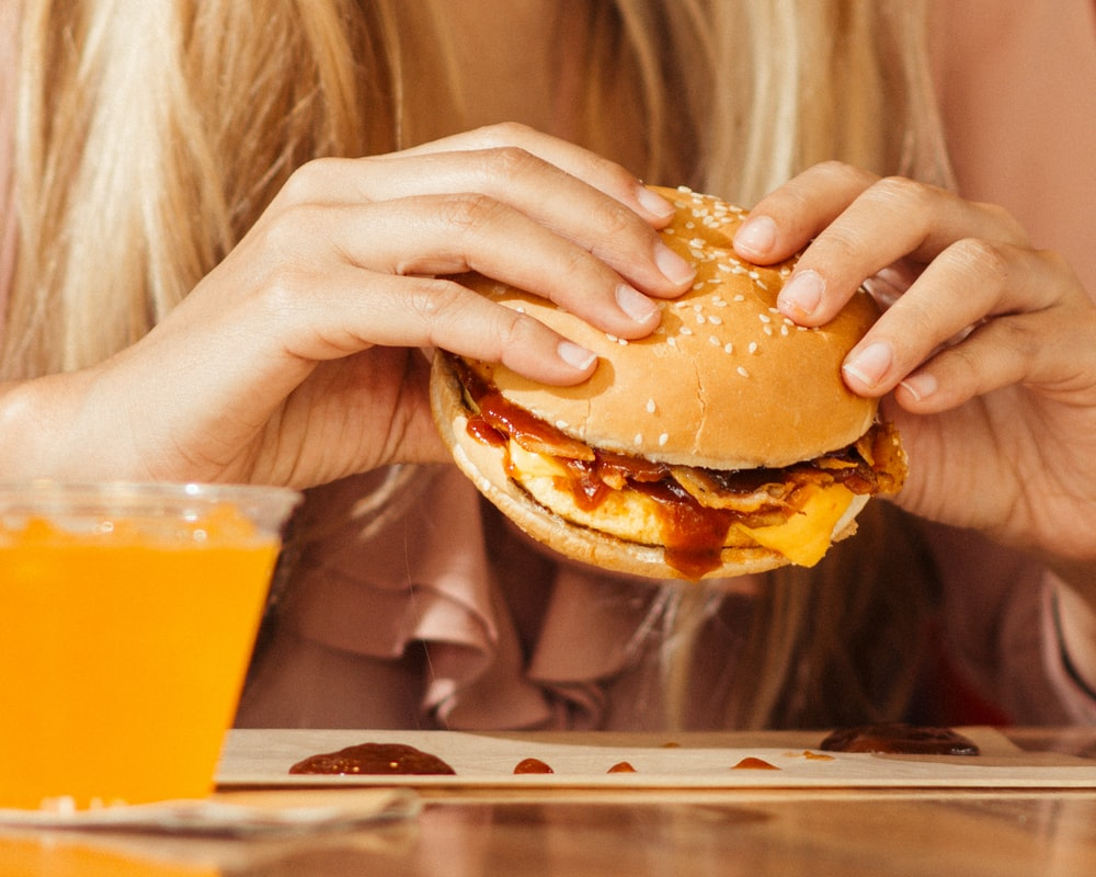 woman holding hamburger on table