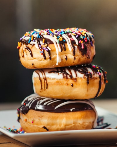 three chocolate-coated donuts with sprinkles