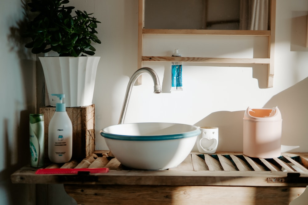 white and teal ceramic sink with gray faucet