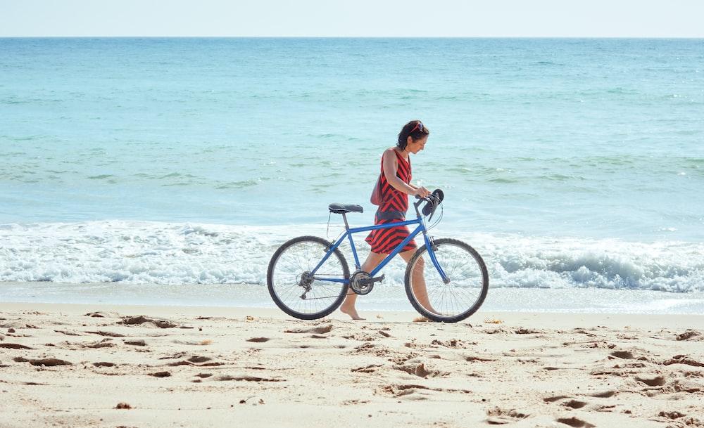 woman walking on seashore with bicycle